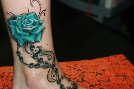 Beads, cross and rose tattoo