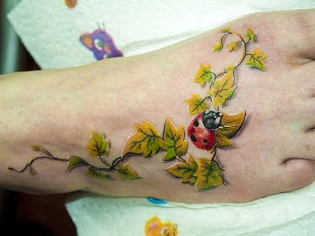 Ladybug on branch tattoo