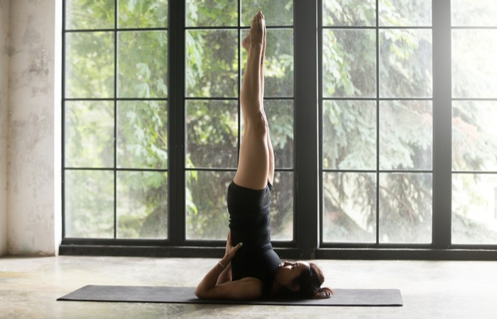 young-woman-practicing-yoga-home-standing-701411257
