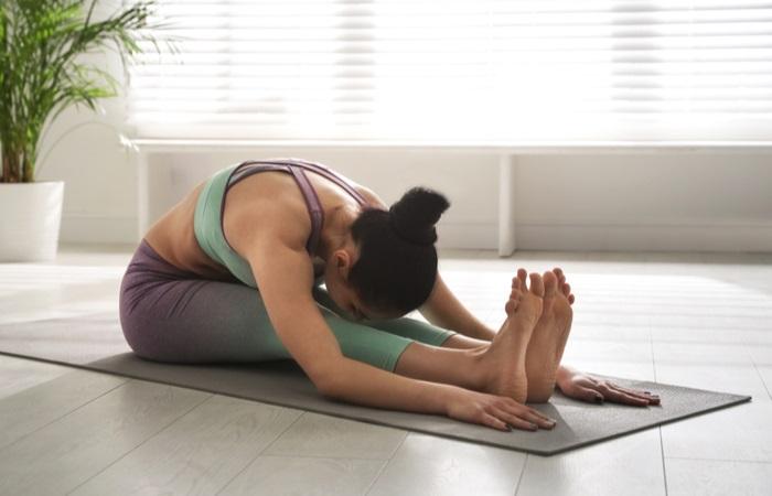 woman-practicing-seated-forward-bend-asana-1615372096
