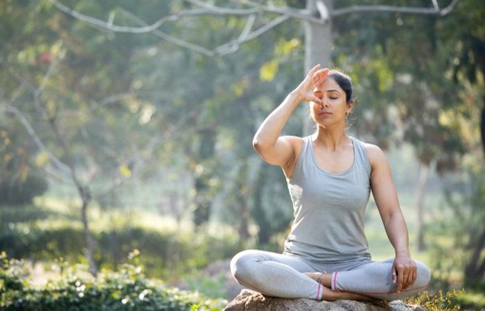 woman-practicing-yoga-lotus-position-park-1669079605
