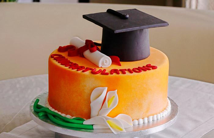 Orange Icing And Vanilla Flavored Cake With Graduation Cap
