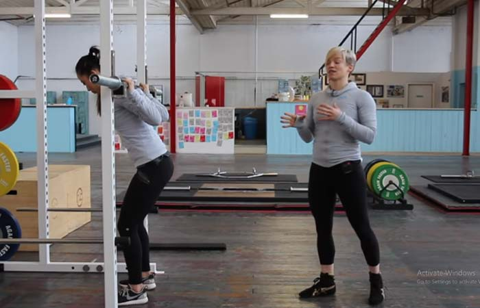 Bring your right foot close to your left and place your shoulders against the barbell