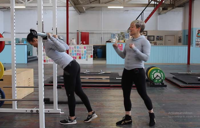 Grip the bar, take a step forward with your left foot, and go underneath the barbell.