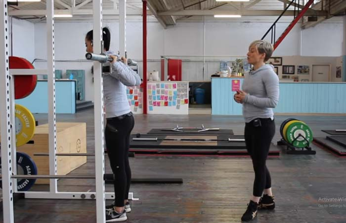 Push through the knees to stand straight up and lift the barbell off the rack